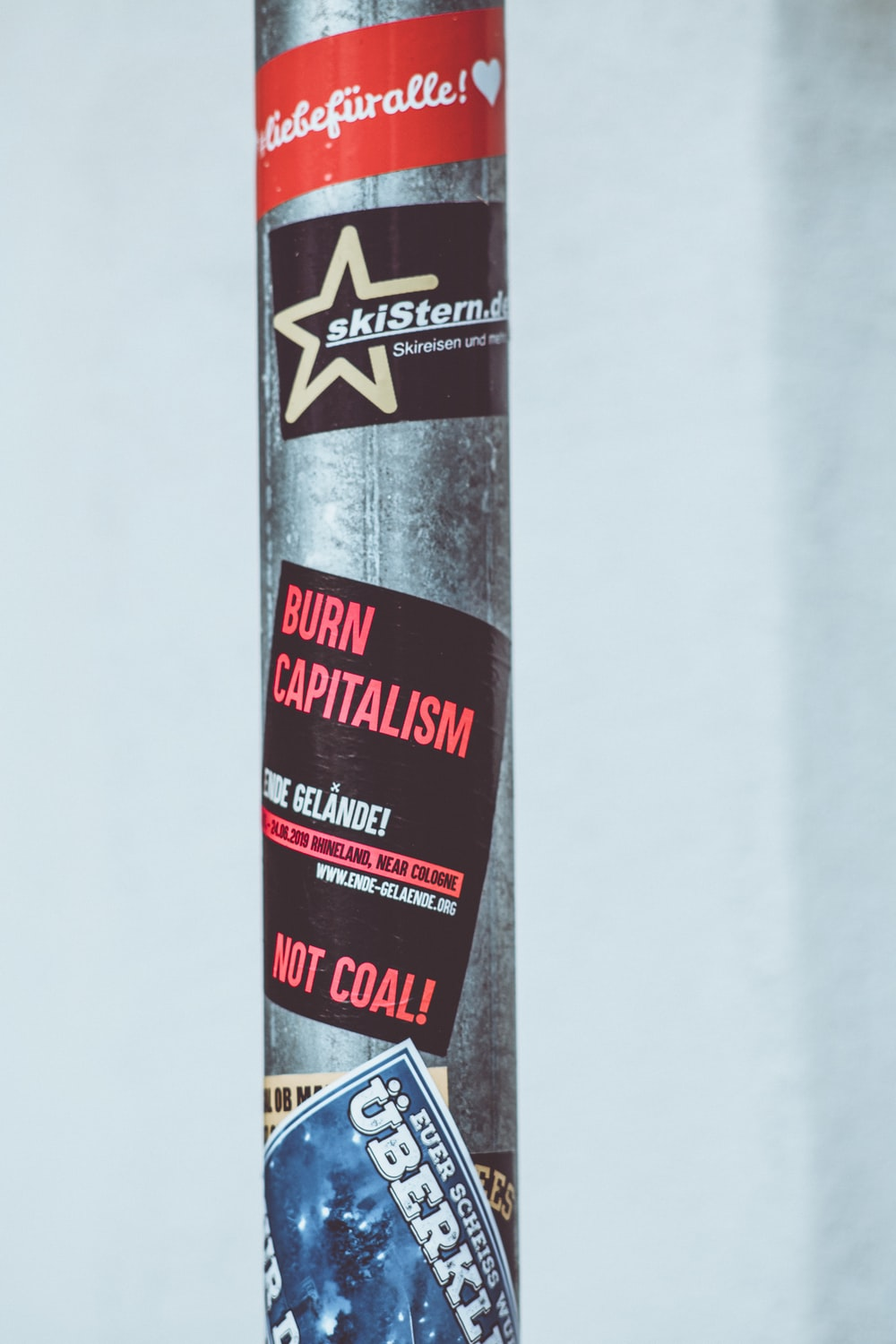 stickers on a gray metal pole