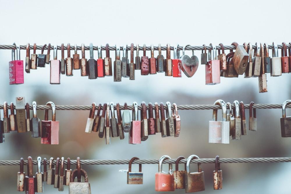 minimalist photography of hanging love padlocks