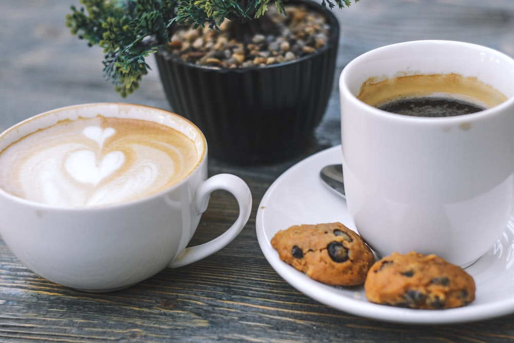 cup of black coffee and two cookies on saucer