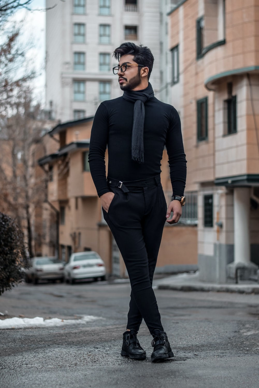 man in black dress shirt, necktie, and pants standing on street