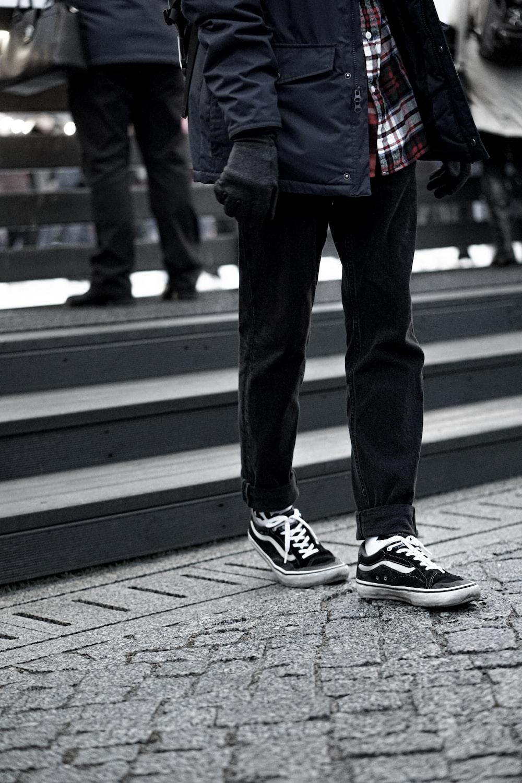 man wearing black Vans sneakers