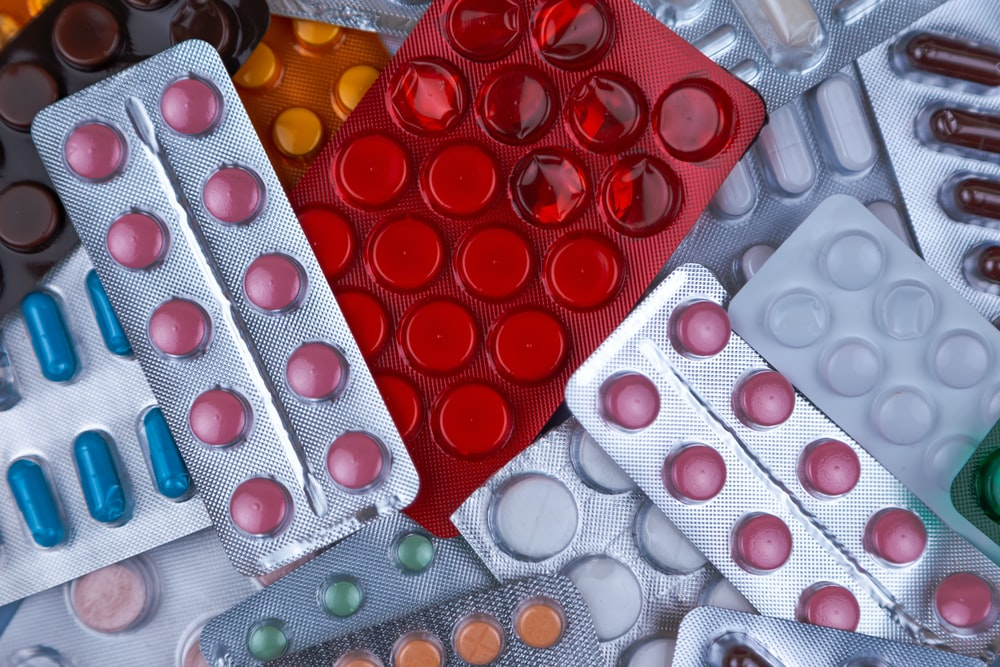 pile of blister packs of colorful medicine tablets