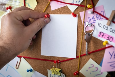 search concept. Close-up view of a detective board with evidence. In the center is a empty mock up white sheet attached with a red pin