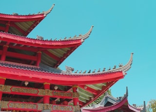 low-angle photography of red and green pagoda building under a calm blue sky