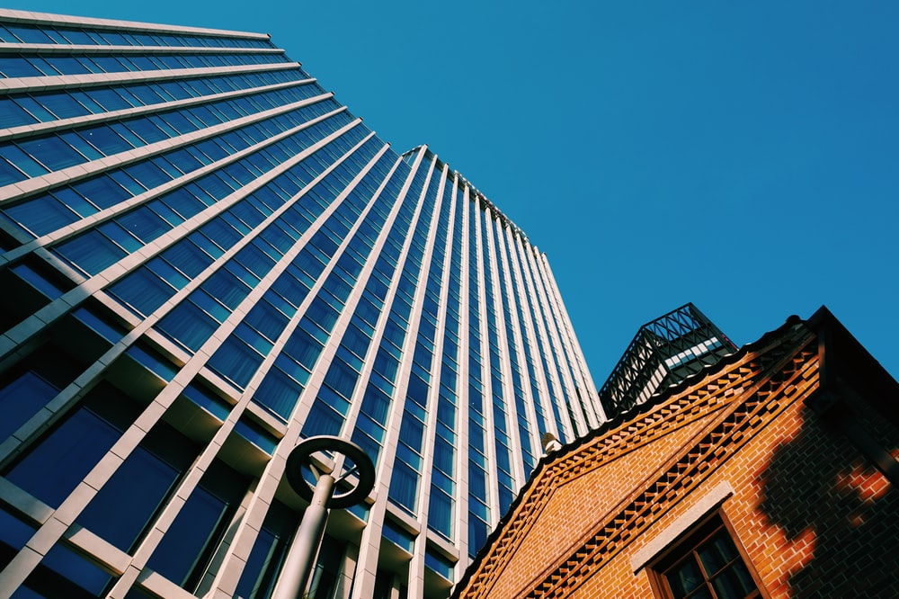 low-angle photography of blue glass walled building during daytime