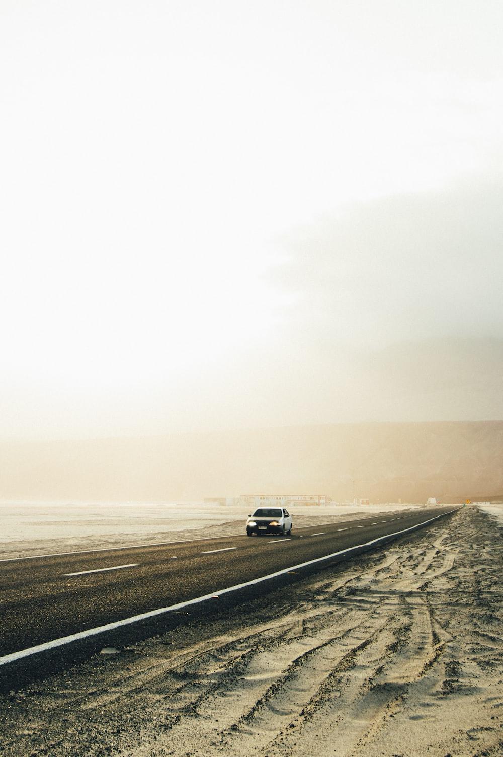 white car on gray asphalt road during daytime