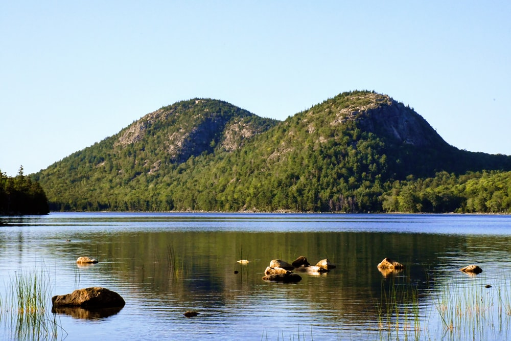 rock formations on body of water viewing mountain during daytime