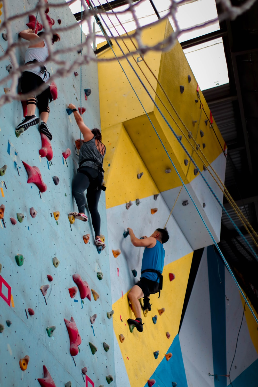 three people climbing on wall