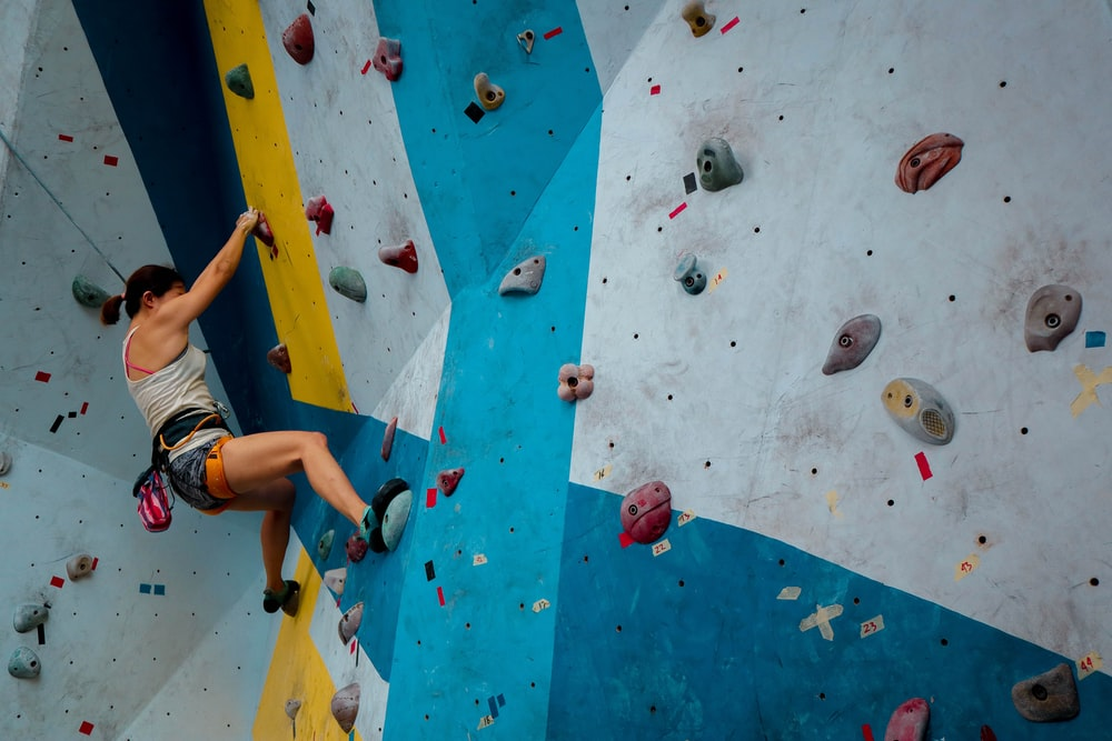 person in white tank top rock climbing