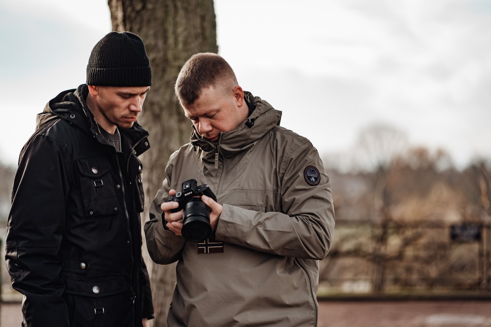 shallow focus photo of man in gray windbreaker hoodie