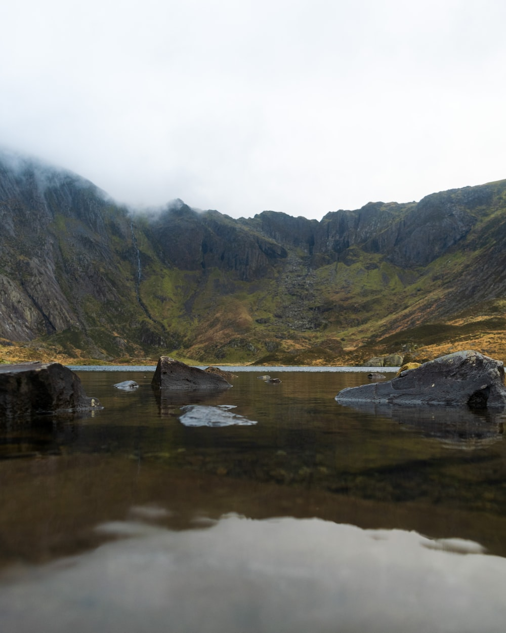 gray rock formations on body of water viewing green field and mountain under white sky