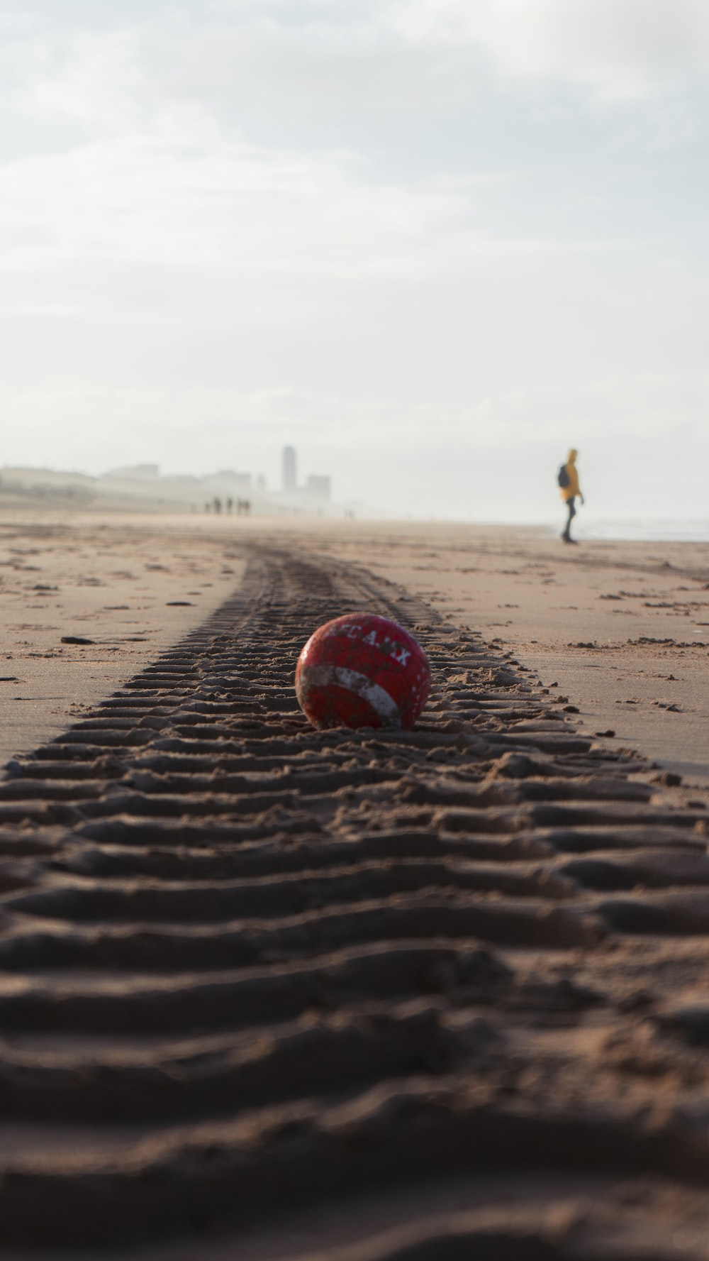 red and white soccer ball on brown sand during daytime