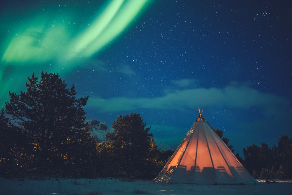 tipi tent on snowfield near trees during night