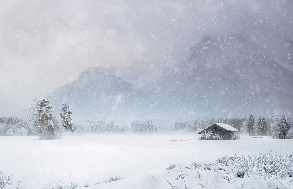 house covered with snow near mountain