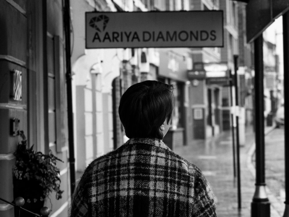 grayscale photography of person under Aariya Diamonds sign