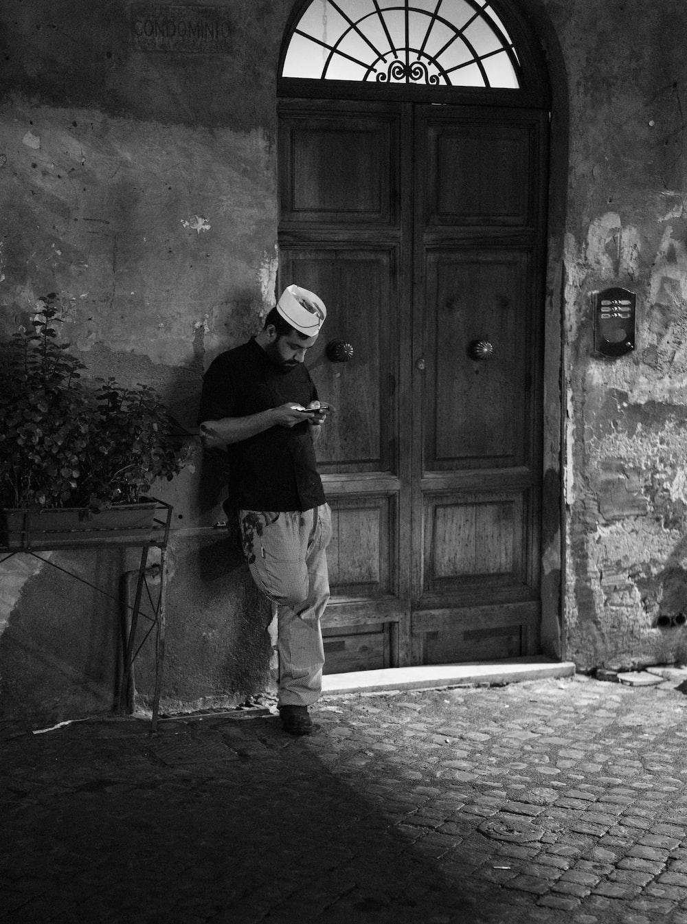 grayscale photo of man standing beside wooden door