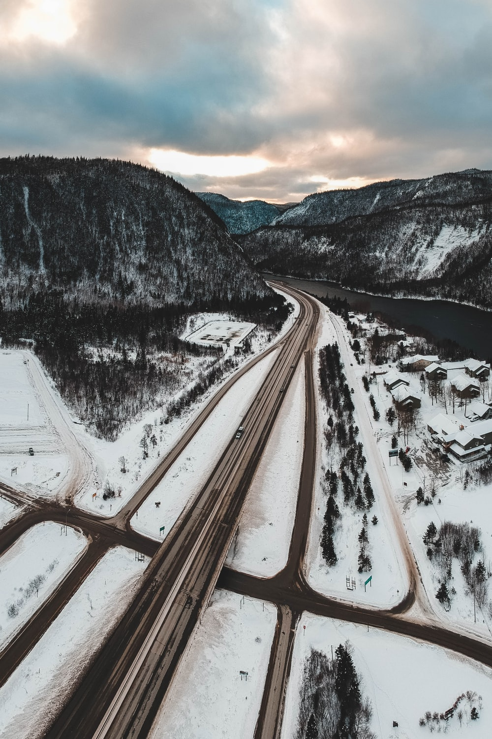 road near river and mountain covered with snow during daytime