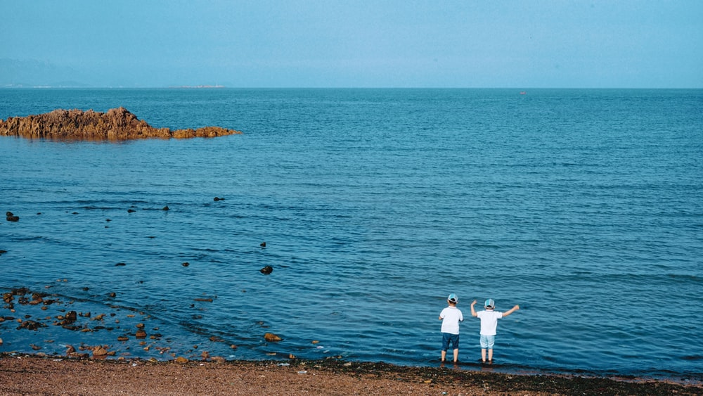 two children standing in front of body of water