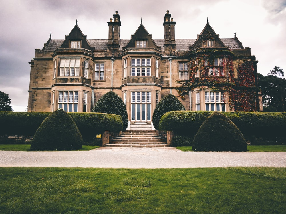 low-angle photography of brown mansion under a cloudy sky during daytime