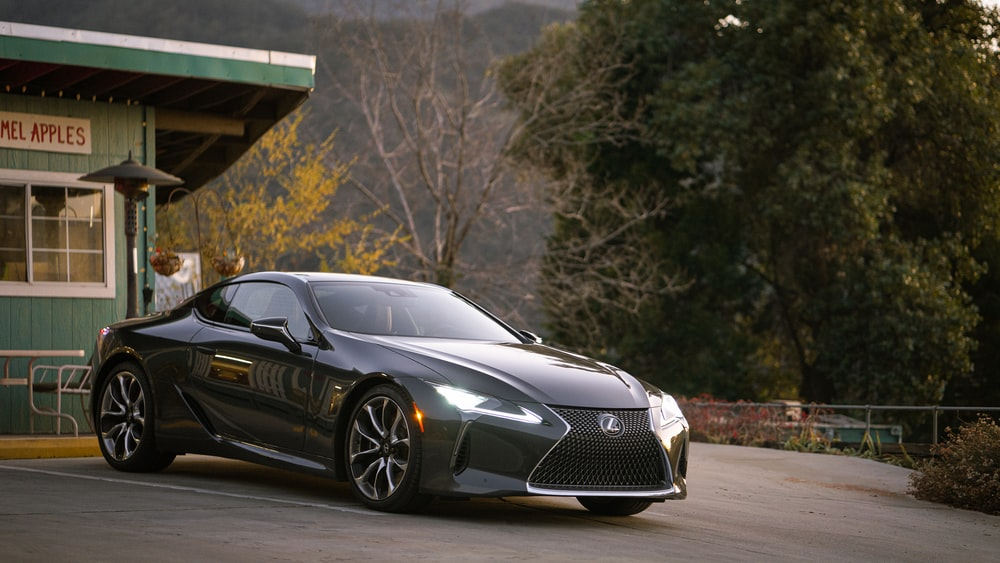gray Lexus coupe parked in front of building