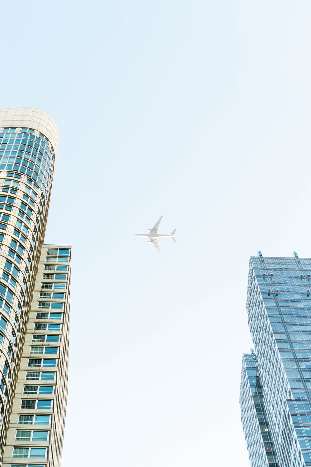 airplane flying above high-rise buildings