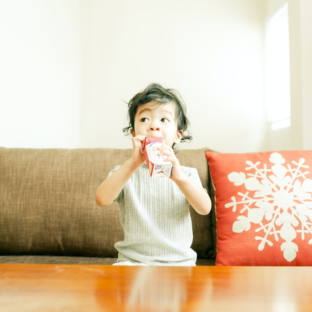 boy sitting on sofa and drinking from juicebox