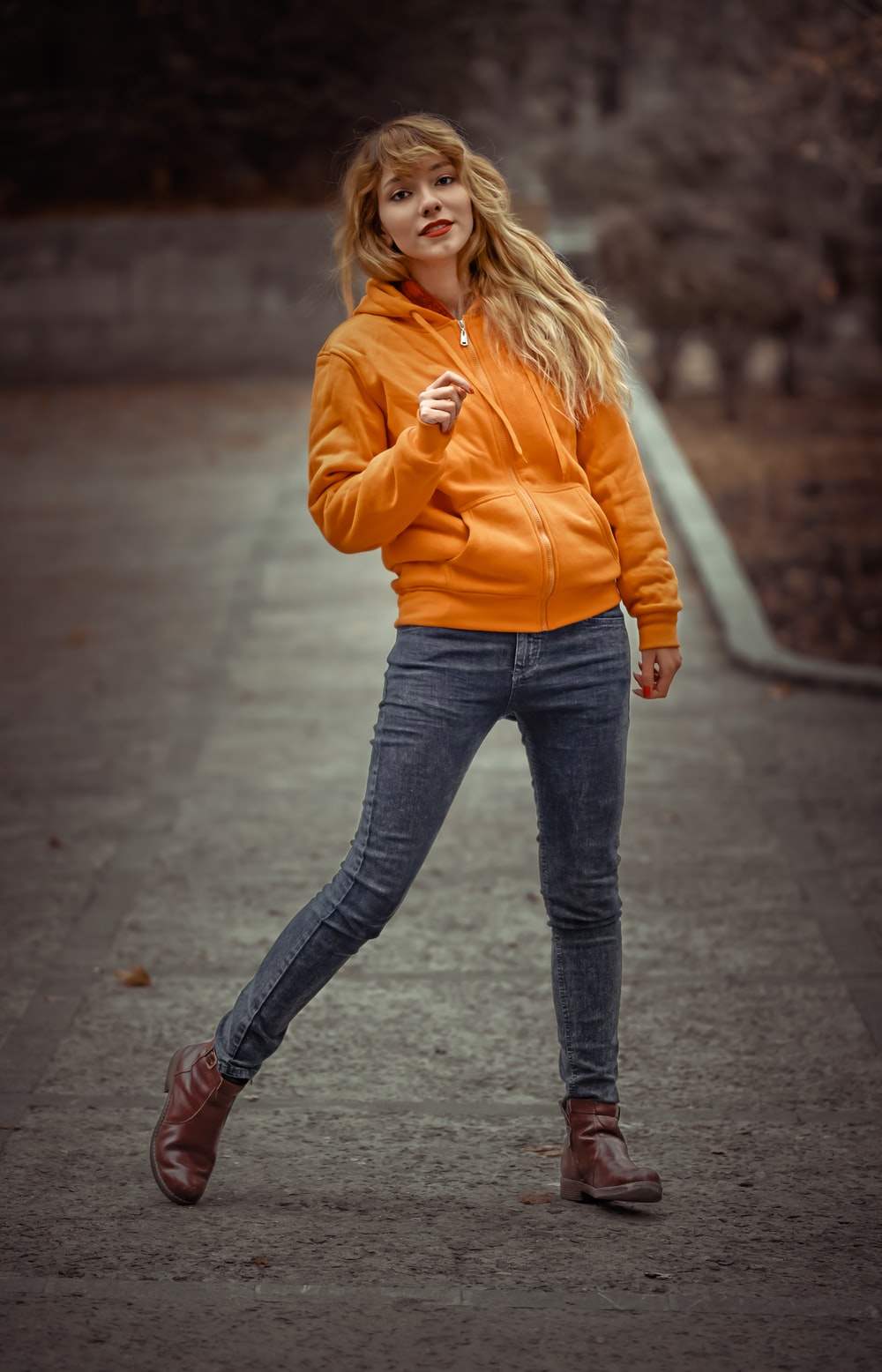 woman in orange jacket and blue jeans standing outdoors