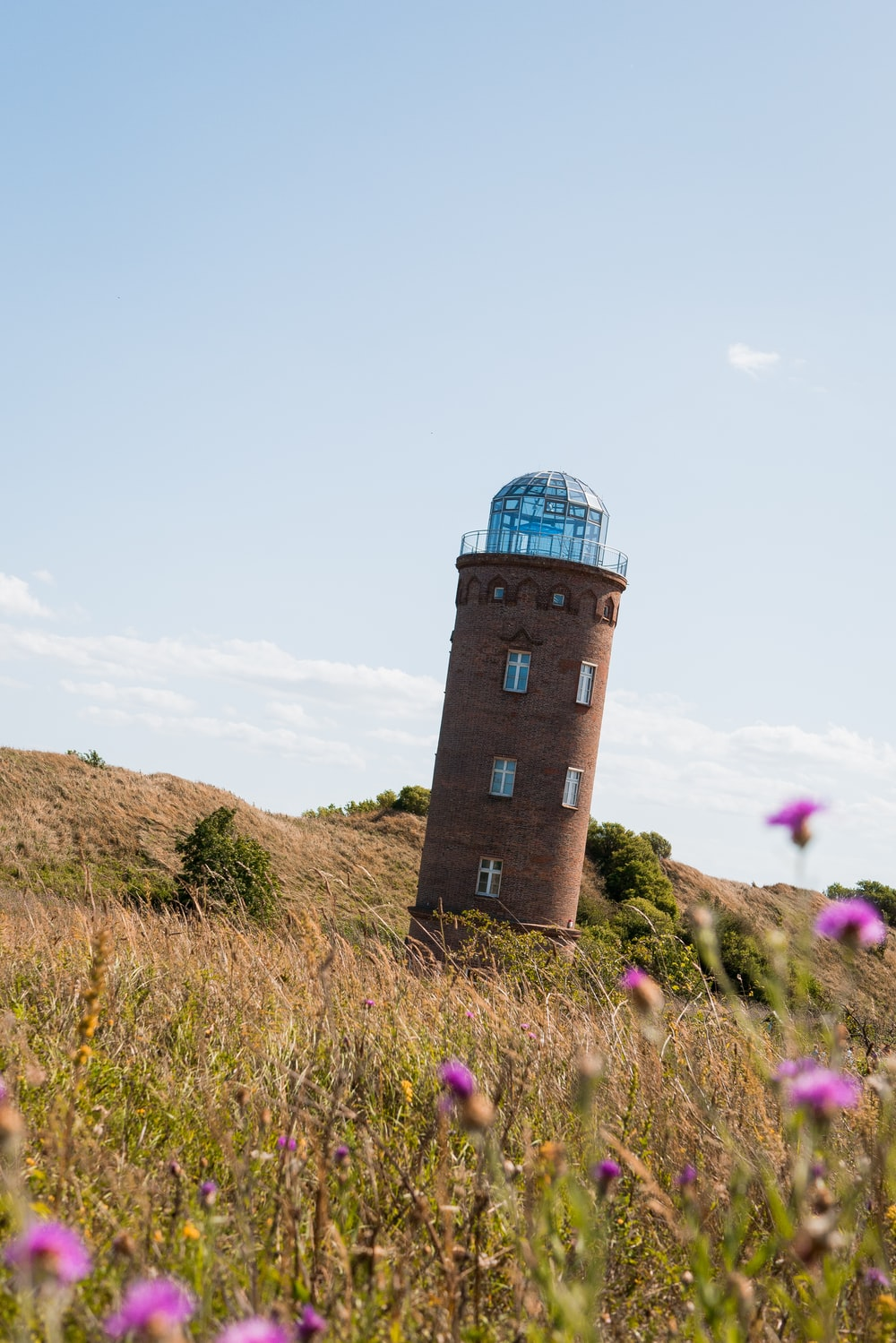 brown lighthouse on brown field under blue and white sky