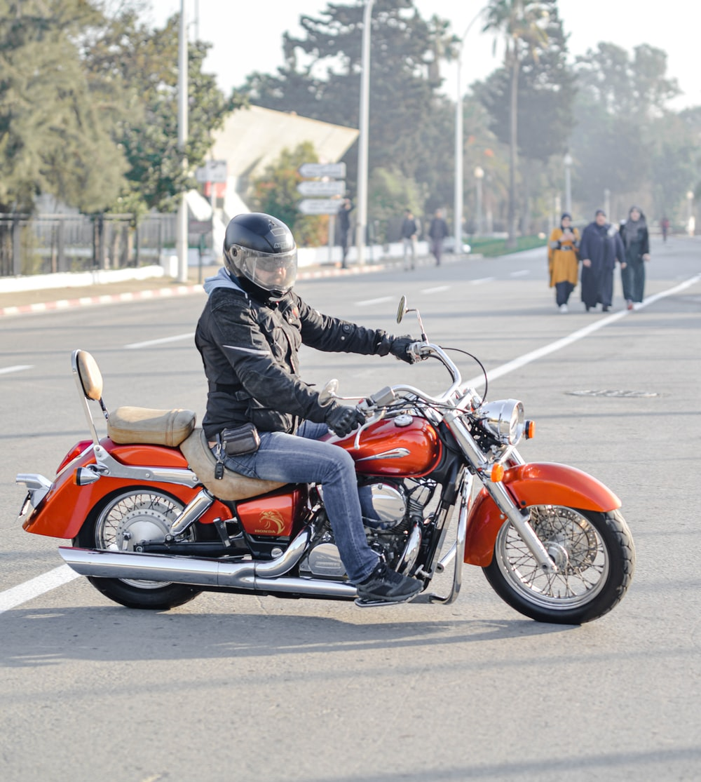 man riding motorcycle on road near people during day