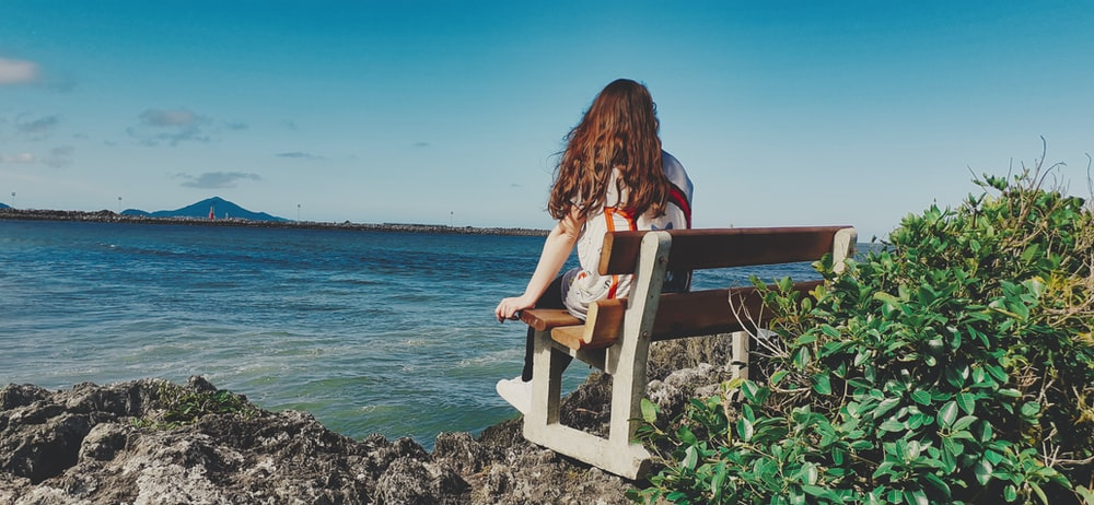 woman wearing white jacket sitting on white wooden bench facing body of water viewing mountain under blue and white sky