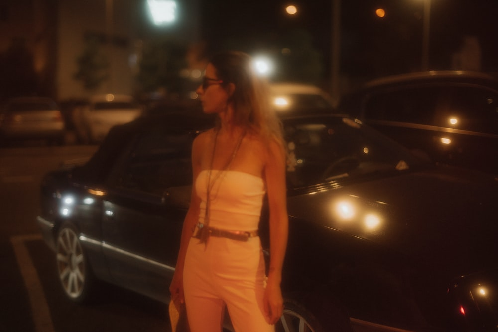 woman wearing white tube standing near black vehicle during night time