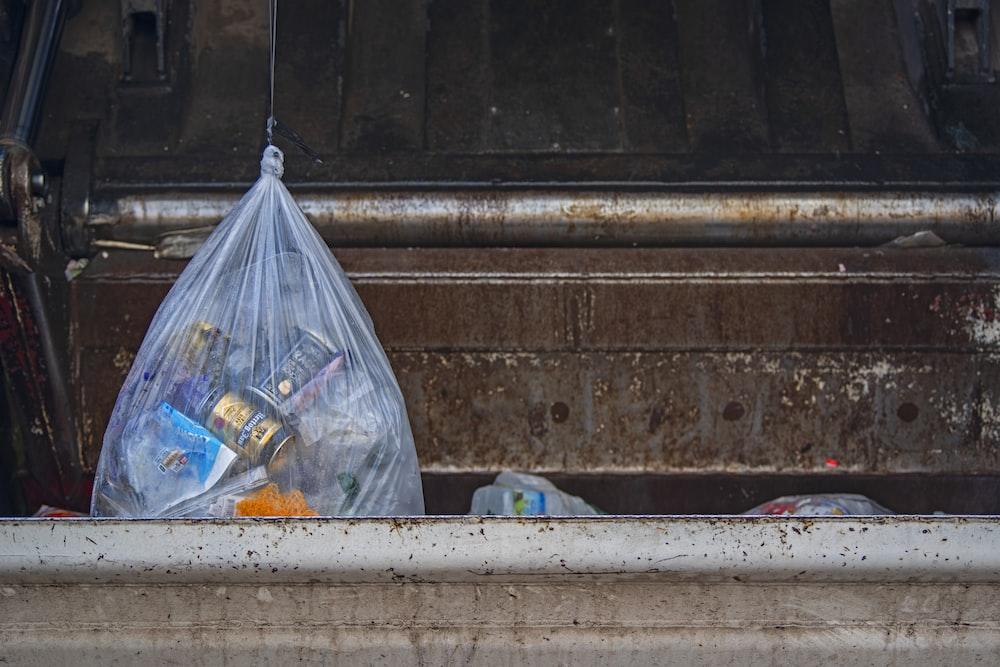 bag of waste in dumpster