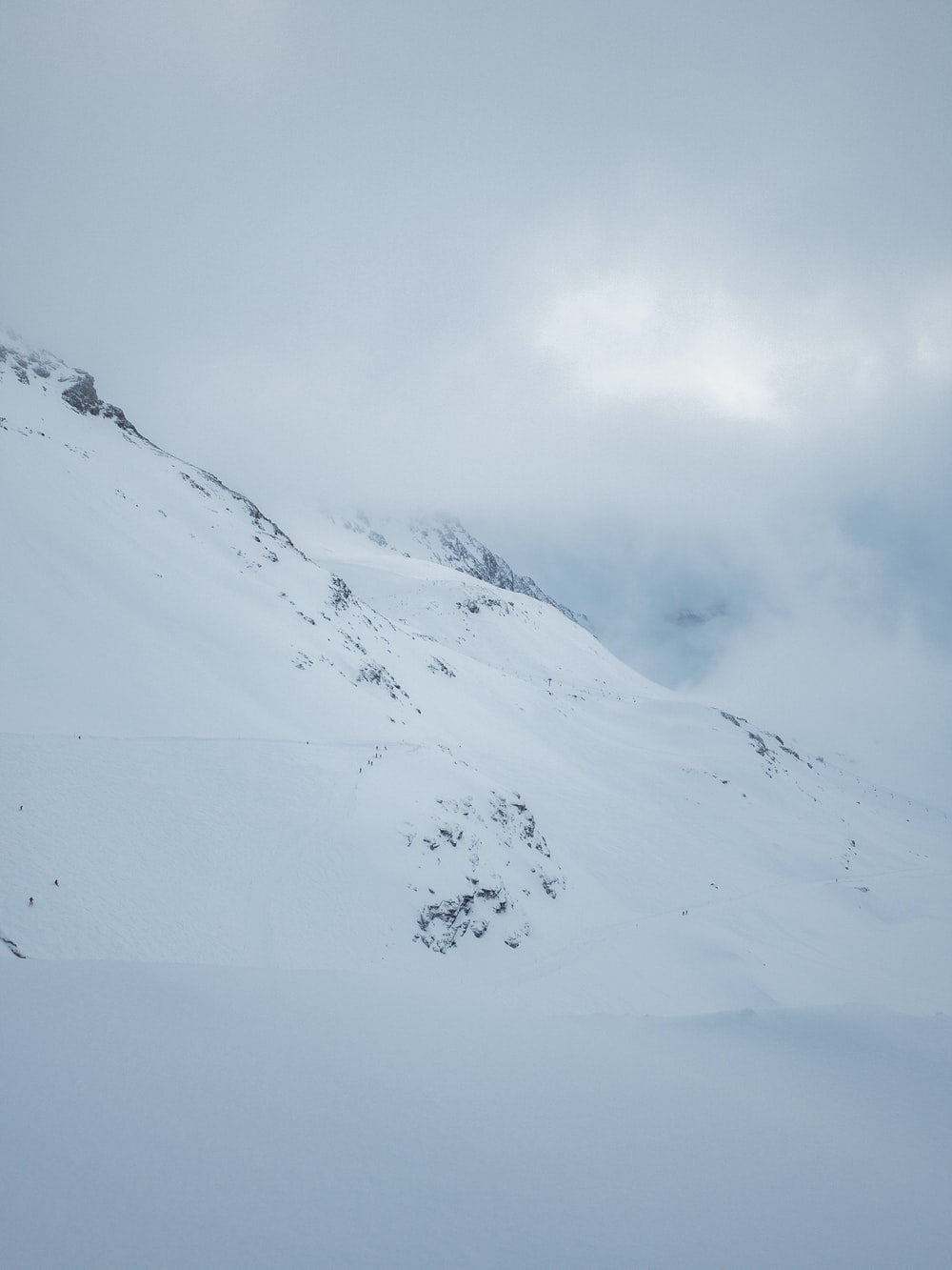 snow-covered mountains under heavy clouds