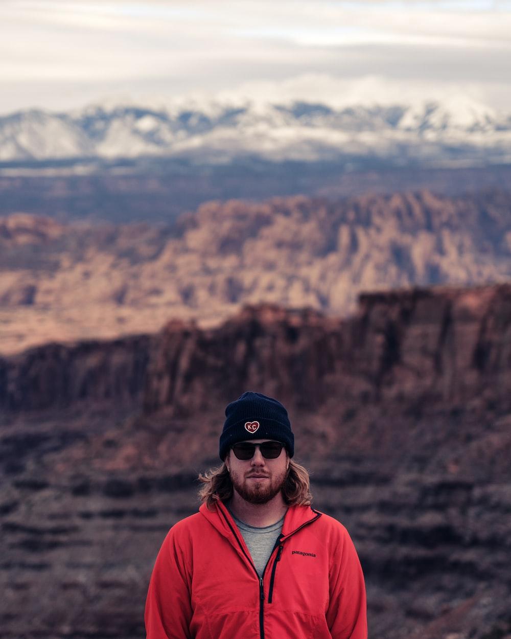 man wearing red zip jacket near mountains during day