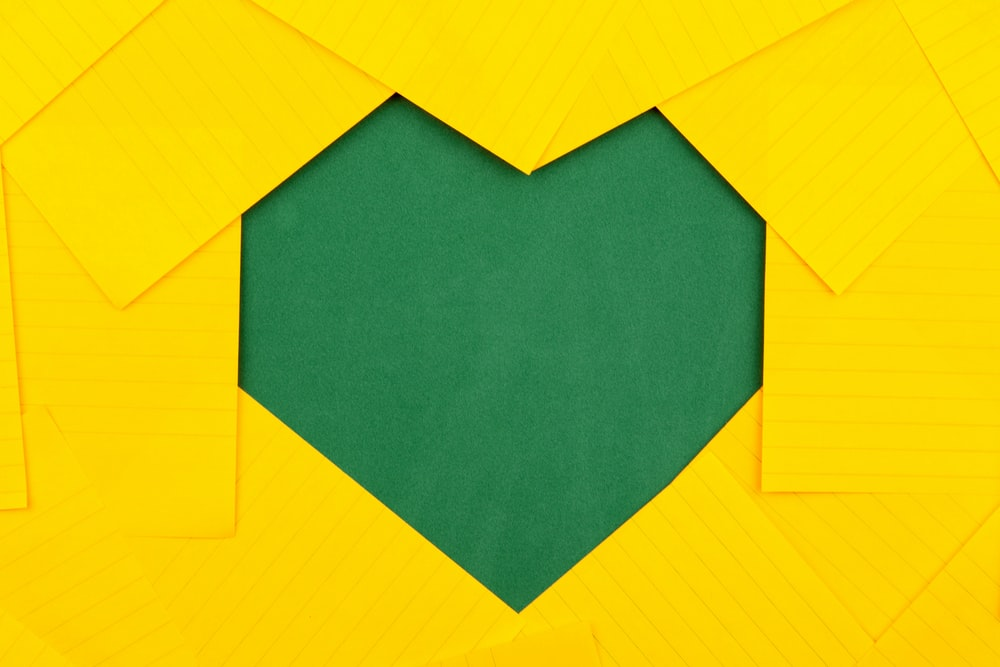 yellow papers forming green heart hole