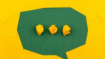 write three crumpled yellow papers on green surface surrounded by yellow lined papers