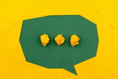 three crumpled yellow papers on green surface surrounded by yellow lined papers write teams background