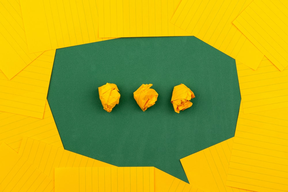 three crumpled yellow papers on green surface surrounded by yellow lined papers