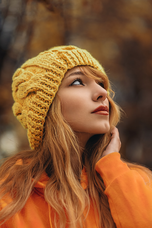 woman in yellow beanie hat and orange sweatshirt
