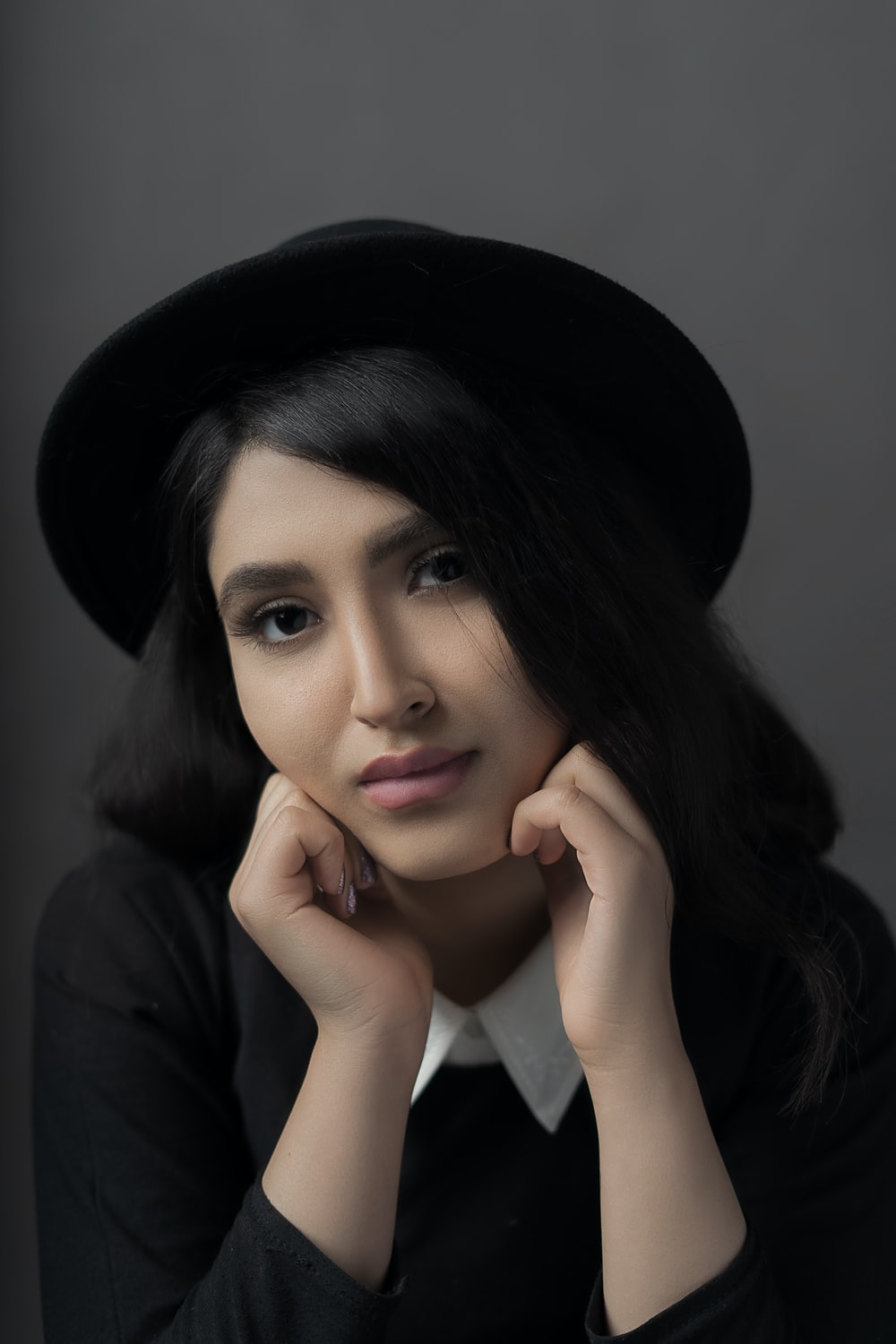 woman in black and white collared top and black hat