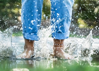 person in blue jeans splashing water through feet
