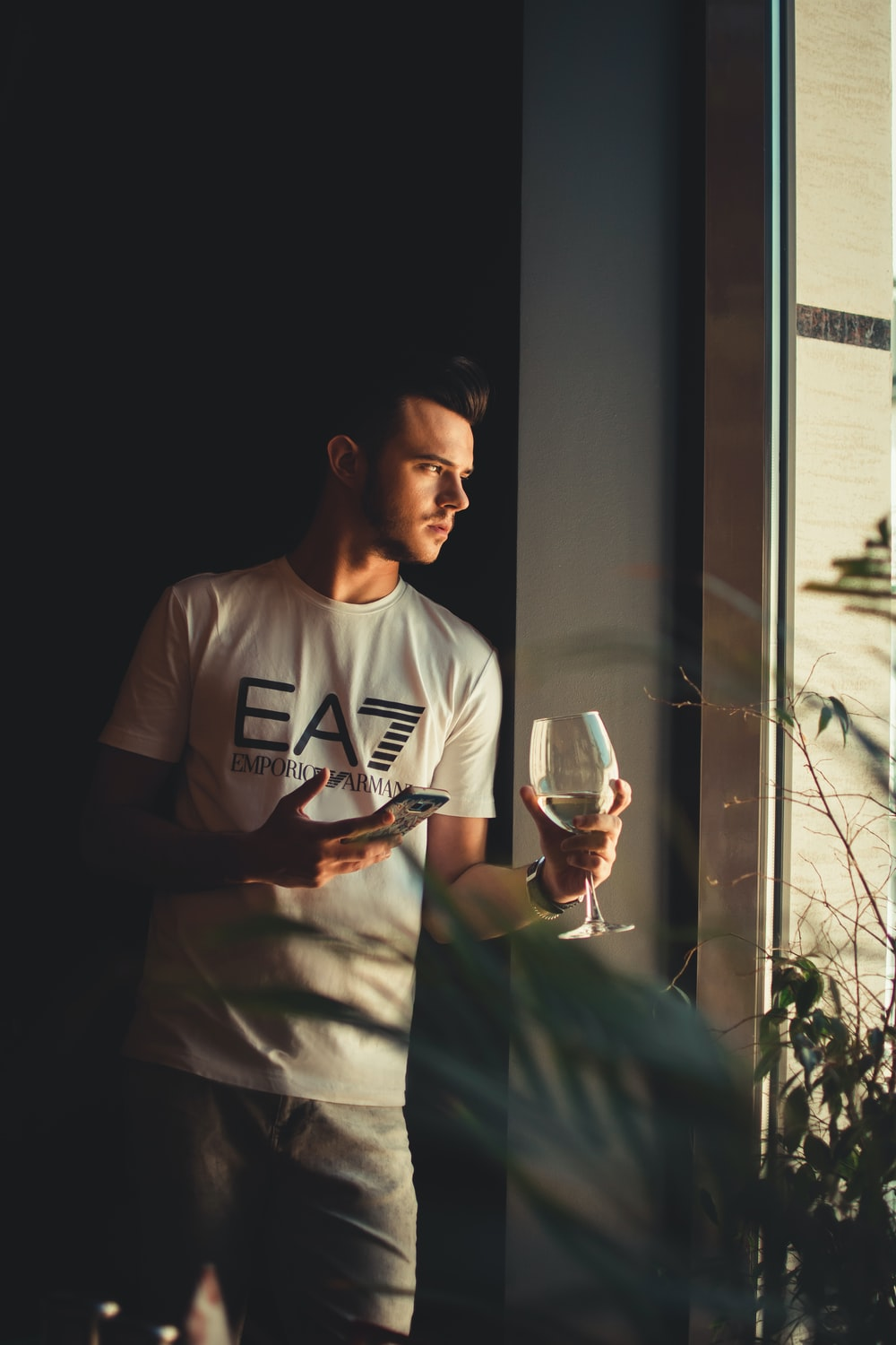 man in white EA7 t-shirt holding wine glass beside window