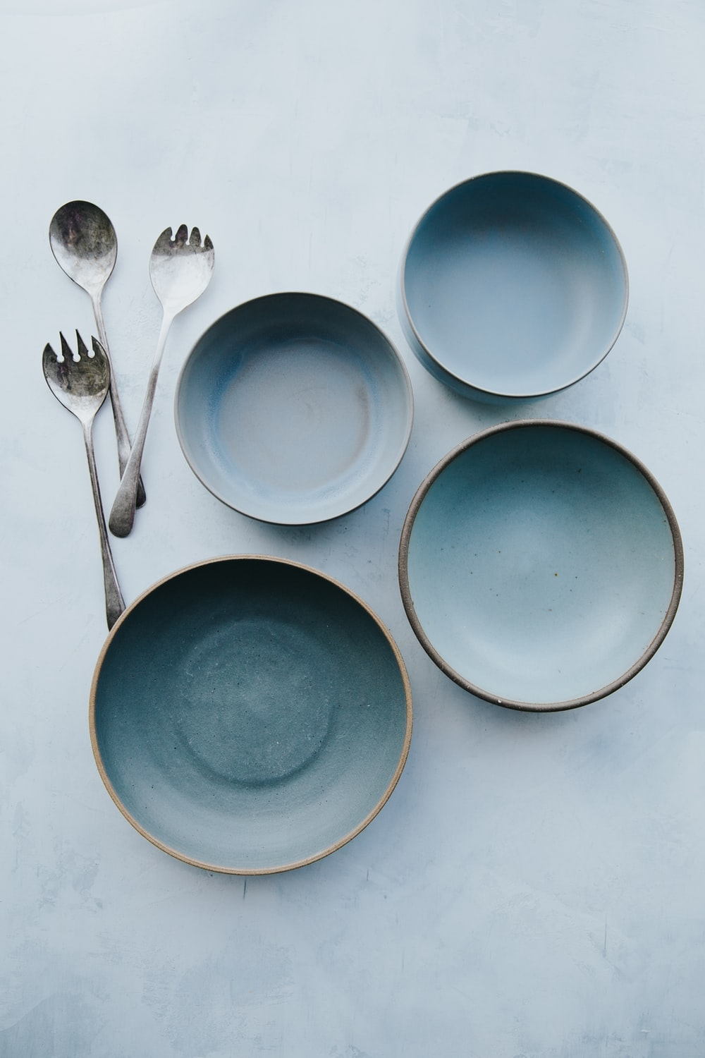 four assorted blue plates on white surface