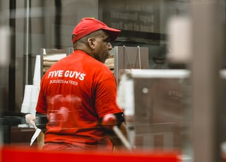man in red shirt and cap inside kitchen