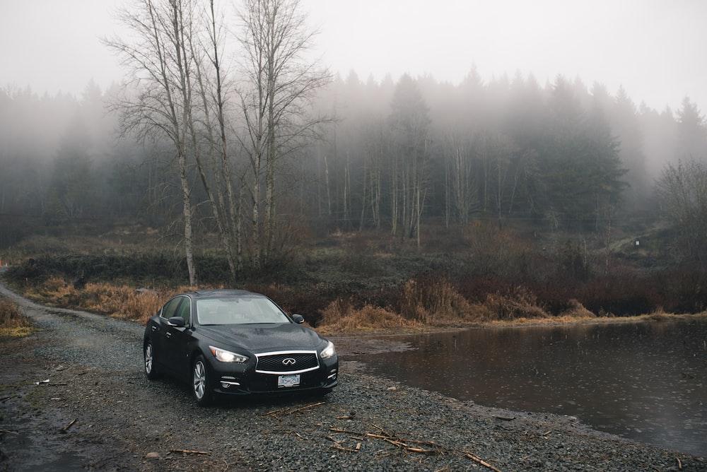 black sedan parked beside body of water during daytime