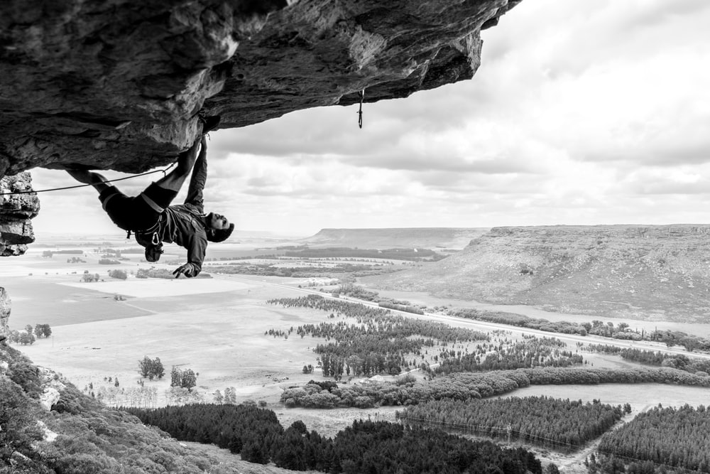 grayscale photo of man rock climbing