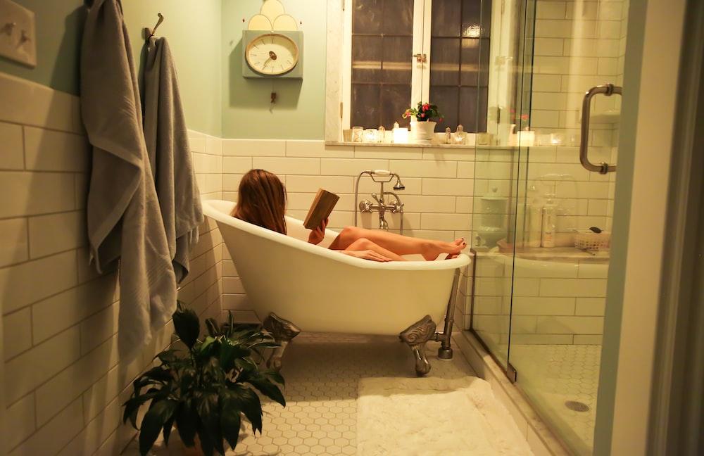 person in white ceramic bathtub