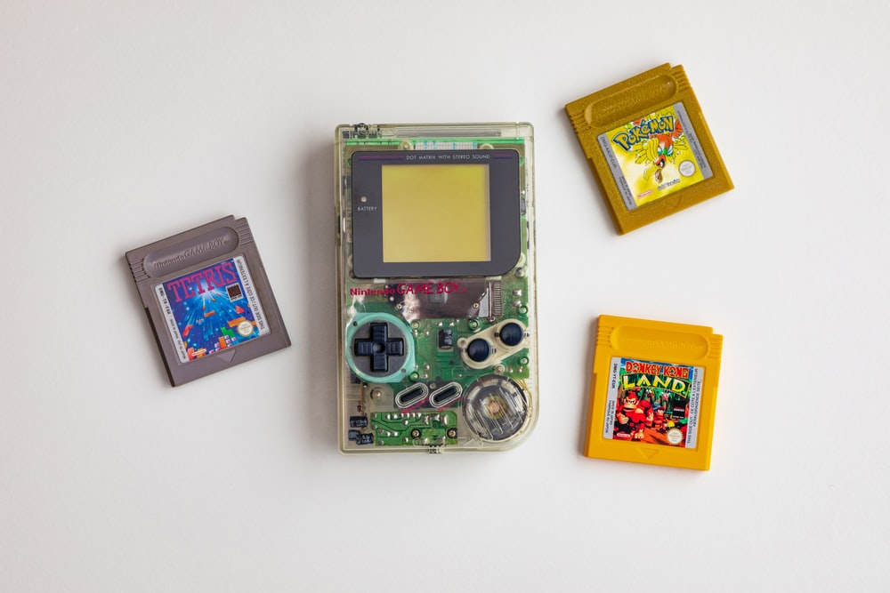 clear and green Nintendo GameBoy on white surface