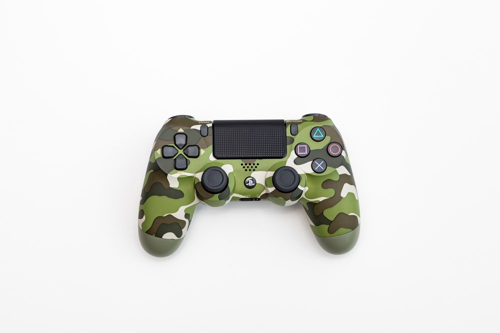 green, black, and white camouflage Sony DualShock 4 wireless controller