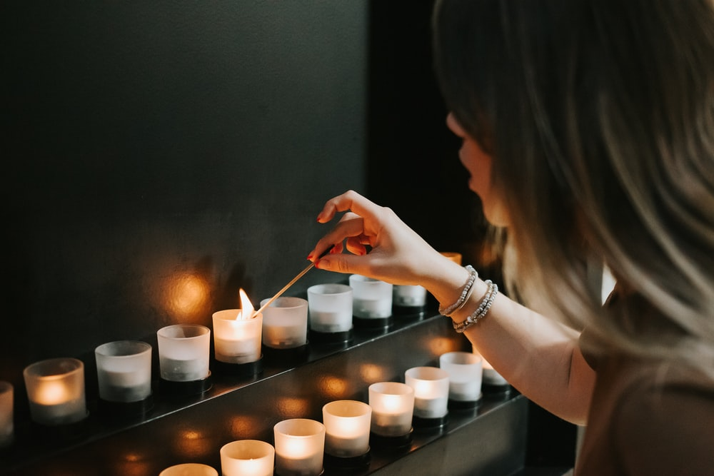 woman lighting a candle beside candles